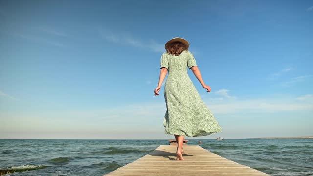 eine junge frau in einem grünen sommerkleid und einem strohhut in zeitlupe läuft morgens im wind an einem holzsteg auf dem meer entlang. gehen gnade schönheit und weiblichkeit - jahreszeit stock-videos und b-roll-filmmaterial