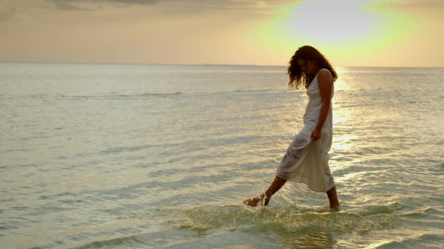 vídeos de stock e filmes b-roll de a young woman in a light summer dress is walking along the edge of the water against the background of the sea and sunset. a great vacation. 10 bit slow motion video - descalço