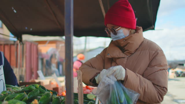 A young woman in a mask buys farm products at the vegetable market A young woman in a mask buys farm products at the vegetable market. small business saturday stock videos & royalty-free footage