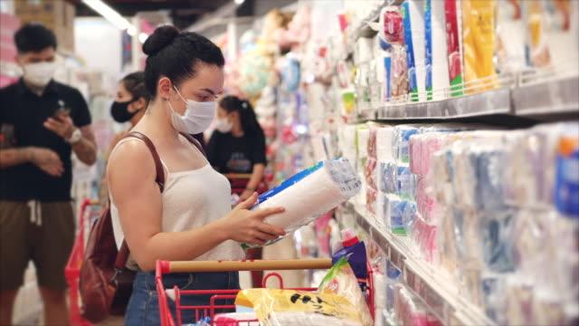 la giovane donna mascherata da un'epidemia di coronavirus fa acquisti in un supermercato, sceglie la carta igienica, le persone in preda al panico dall'epidemia globale stanno comprando tutto. - consumismo video stock e b–roll
