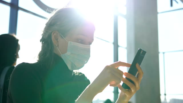 A young woman in a medical mask sits with a phone at the airport and waits for departure. - vídeo
