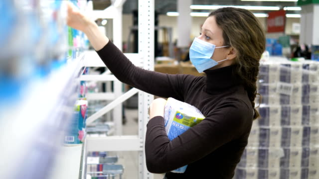 A young woman in a medical mask takes a lot of toilet paper in a supermarket - vídeo