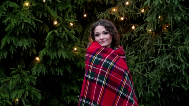 young woman in a plaid against a christmas tree background and garlands video