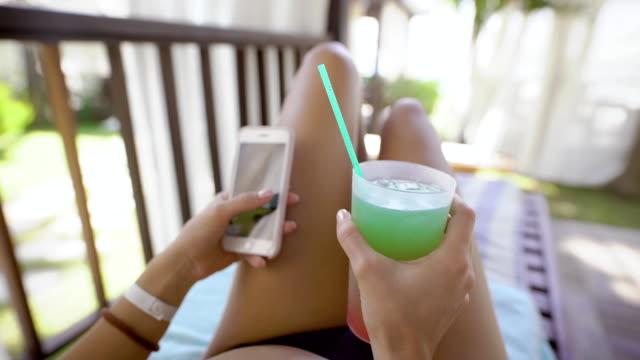 水着姿の若い女性が休暇中、女性の多くのデッキチェアに横になっているが、カクテルと携帯電話を保持しています。 ビデオ