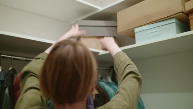 en ung kvinna i en garderob tar en låda med skor från hyllan. - looking inside inside cabinet bildbanksvideor och videomaterial från bakom kulisserna