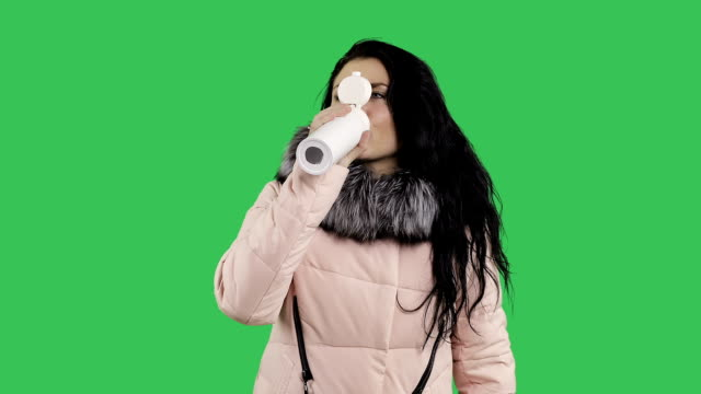 A young woman in a winter coat goes and drinks tea from a thermo mug. video