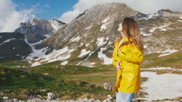 Young woman in a yellow raincoat walking on the road with beautiful mountains background, slow motion
