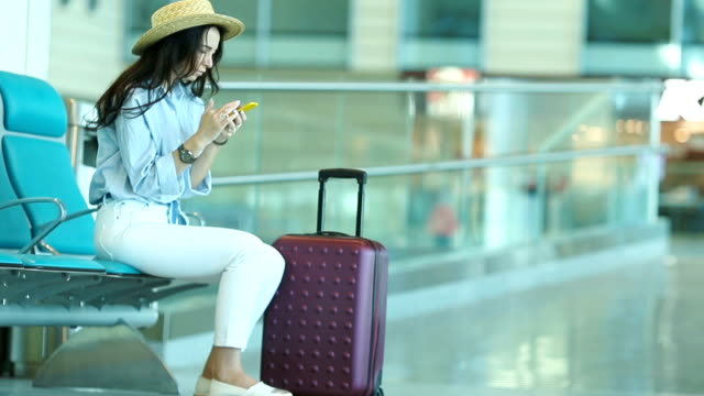 Young woman in an airport lounge waiting for flight aircraft. Caucasian woman with smartphone in the waiting room video