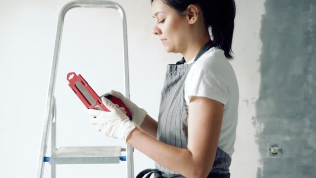 Young woman in an apron and gloves pulling a spatula from a case before work