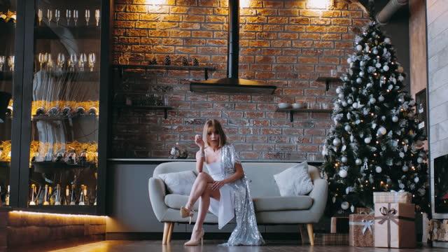 en ung kvinna i en aftonklänning sitter ensam i en soffa på julafton. - aftonklänning bildbanksvideor och videomaterial från bakom kulisserna