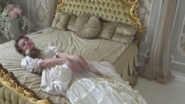 stockvideo's en b-roll-footage met jonge vrouw in bal jurk valt op de gouden ingerichte bed close-up. meisje is moe en slaperig. vrouw na bal rusten. - middeleeuws