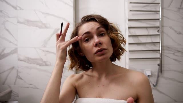 Junge Frau in Badetuch tun Augenbrauen Make-up im Bad - halten einen Bleistift und erklären, um Kamera, wie man perfekte Augenbrauen zu machen. Morgen Make-up – Video