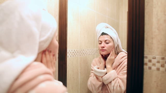 Young woman in bathrobe applying facial moisturizer. video