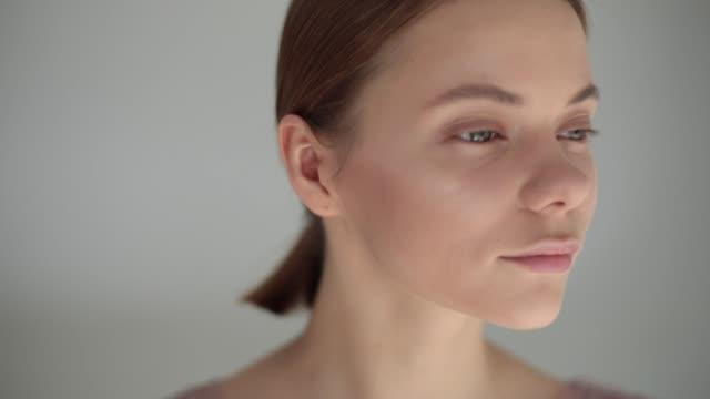 vidéos et rushes de jeune femme dans un salon de beauté fait de maquillage professionnel avec pinceau blush ombres cosmétiques se bouchent. artiste en appliquant le surligneur sur visage féminin ralenti. produits de mode industrie accessoires outils - image teintée
