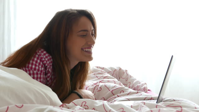 junge frau im bett genießen einen videoanruf - online dating stock-videos und b-roll-filmmaterial
