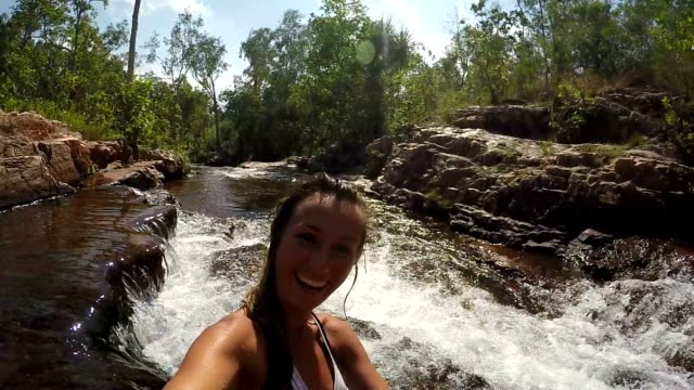 Young woman in bikini takes a selfie with waterfalls video