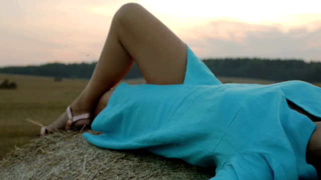 young woman in blue dress lying sexy on a stack of hay. - bassino video stock e b–roll
