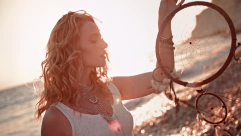 Young woman in boho style with dreamcatcher at beach Young redhead hippie woman with dreamcatcher and silver jewelry relaxing at beach at sunset boho stock videos & royalty-free footage