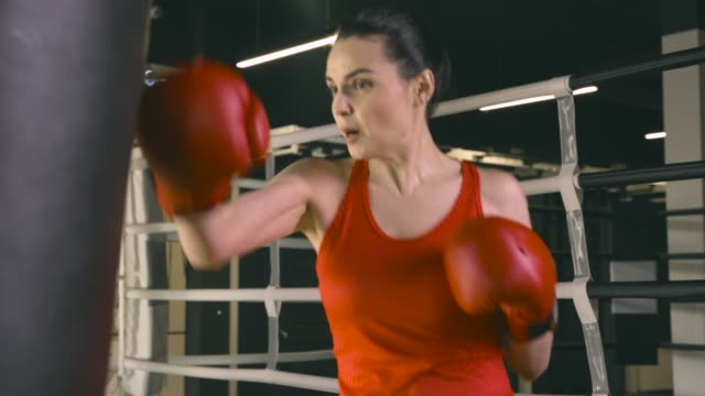Young woman in boxing gloves hitting a boxing bag video