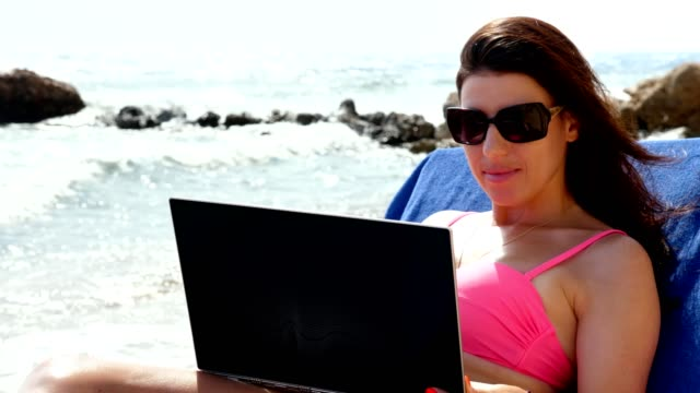 young woman in bright pink swimsuit and sunglasses, uses laptop, lying on lounger, on beach by the sea, hot summer day. freelancer, remote work. summer vacation at sea video