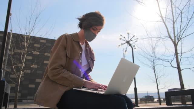junge frau in braunen kleidern und maske arbeitet aus der ferne mit einem laptop im freien - freischaffender stock-videos und b-roll-filmmaterial