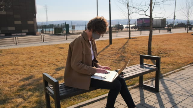 young woman in brown clothes and a mask works remotely with a laptop outdoors - nazionalità russa video stock e b–roll