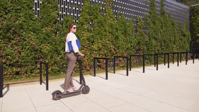 a young woman in business clothes is riding an electric scooter on a sunny summer day, tracking shot. modern eco-friendly mobile mode of transport - monopattino elettrico video stock e b–roll