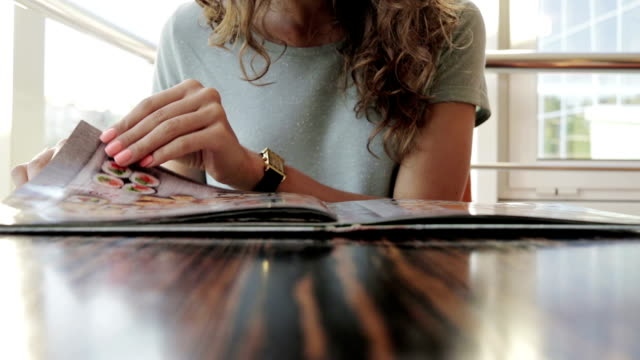 Young woman in cafe chooses lunch Young woman in cafe chooses lunch flipping through the menu menu stock videos & royalty-free footage