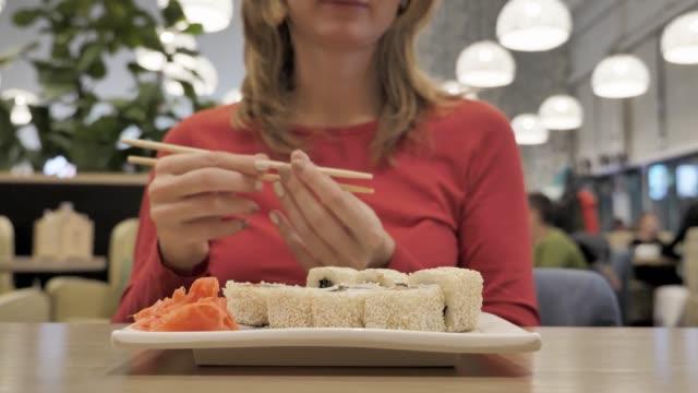箸で寿司を食べてカフェの若い女性 ビデオ
