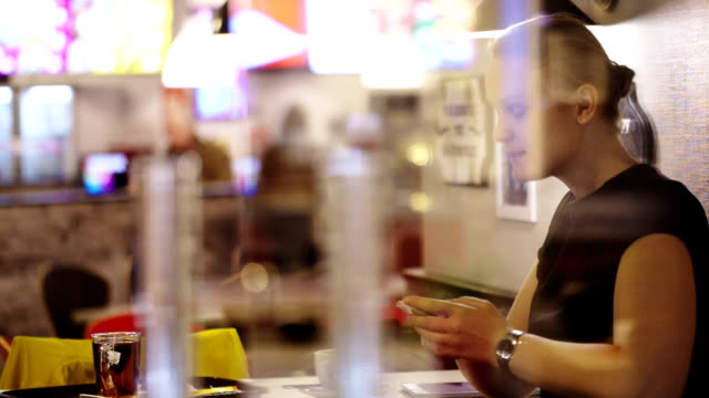 Young woman in cafe thinking over sms and typing it video