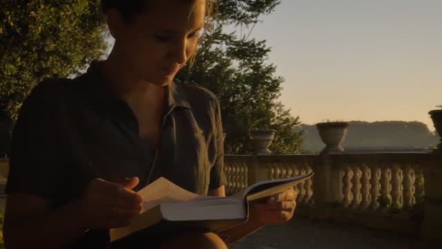 young woman in campidoglio reading a book in front of rome cityscape - peter the apostle video stock e b–roll