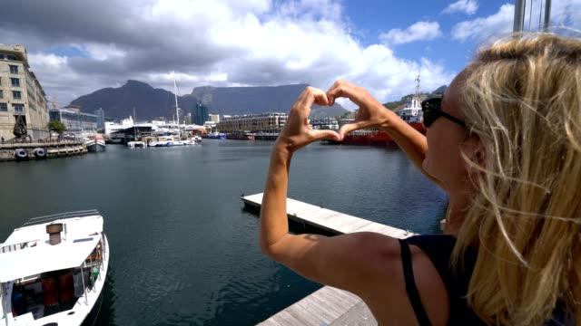 Young woman in Cape Town harbour making heart shape finger frame video