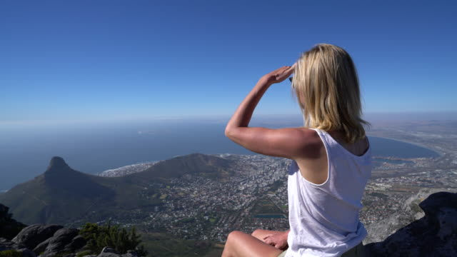 Young woman in Cape Town on top of mountain looking at view Woman hiking in Cape Town South Africa, reaches top of Table Mountain table mountain national park stock videos & royalty-free footage