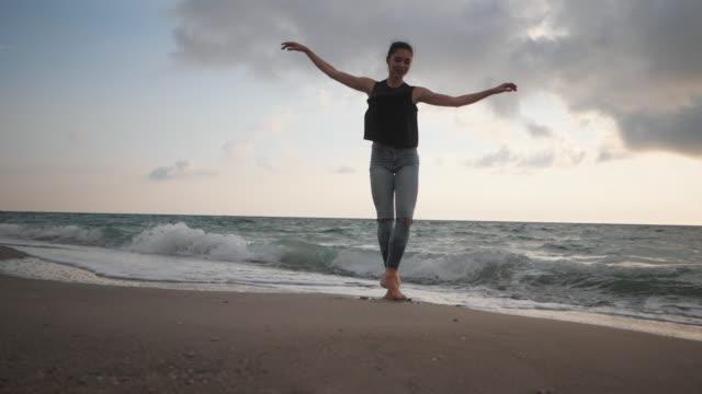 ung kvinna i avslappnad stil - denim och svart topp gör balett på stranden. attraktiva ballerina metoder i stretching på sandiga kusten under hösten. slow motion - balettstång bildbanksvideor och videomaterial från bakom kulisserna