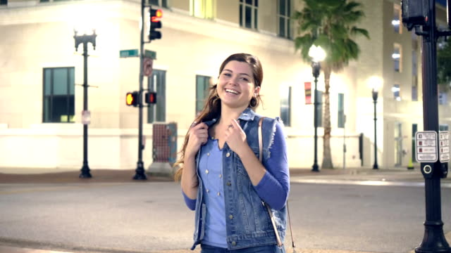 Young woman in city at night, walks up to camera