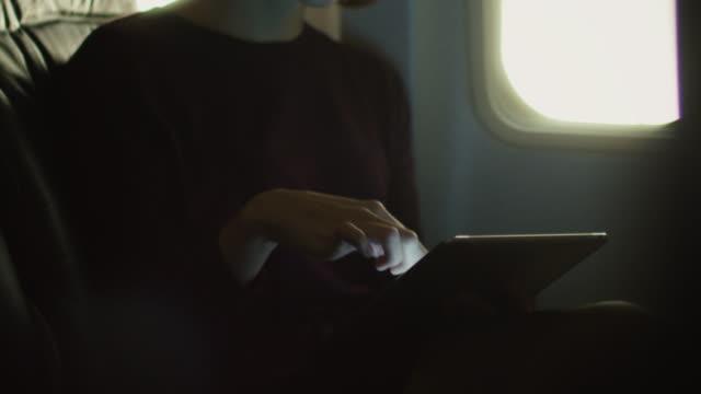 junge frau in nahaufnahme nutzt eine tablette in einem flugzeug neben einem fenster. - tablet mit displayinhalt stock-videos und b-roll-filmmaterial