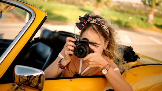 young woman in convertible car taking photos with camera - аксессуар для волос стоковые видео и кадры b-roll