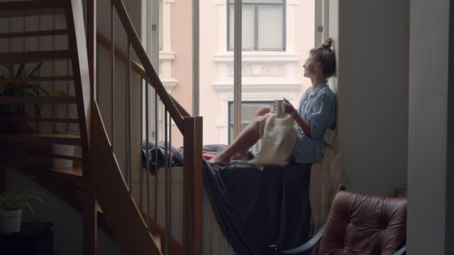 young woman in cosy pajama drink coffee on balcony - время дня стоковые видео и кадры b-roll