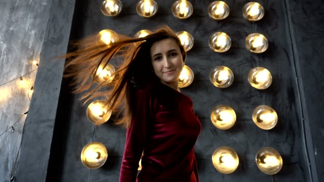 Young woman in dress and beautiful face on a background of wall with powerful lamps Young woman in dress and beautiful face on a background of wall with powerful lamps. Hair of model streamed in the wind. Dolly shot highlights hair stock videos & royalty-free footage