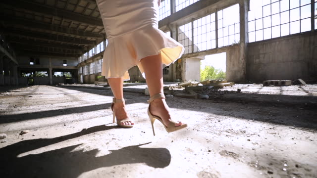 Young woman in elegant dress in abandoned warehouse