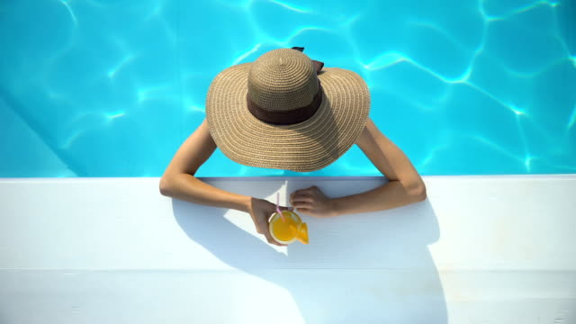 Young woman in elegant hat swimming in pool and enjoying delicious cocktail