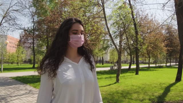 junge frau in gesicht maske walking hund im park im sommer - hundesitter stock-videos und b-roll-filmmaterial