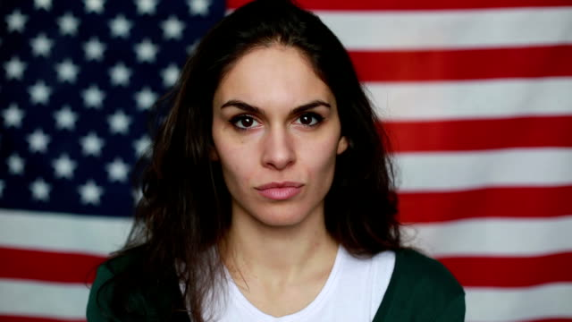 Young woman in front of American Flag video