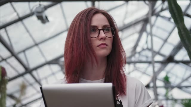 A young woman in glasses, looks into the distance and makes notes.