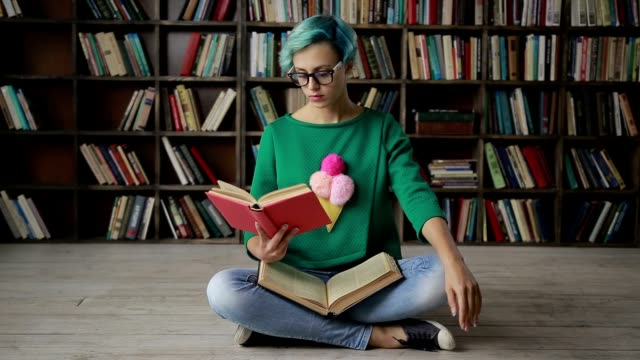 Young woman in glasses reading an interesting book Charming nerdy woman with blue hair in spectacles sitting in lotus posture reading a book over bookshelves background. Attractive hipster girl with a book sitting cross legged, looking away thoughtfully and adjusting eyeglasses. Dolly shot. Slo mo. lotus position stock videos & royalty-free footage