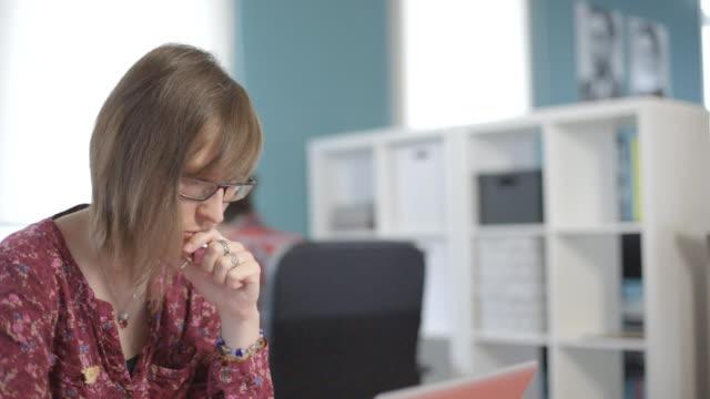 ung kvinna i glasögon som arbetar på kontor med vägg av rack, att sätta sin hand till sina läppar - looking inside inside cabinet bildbanksvideor och videomaterial från bakom kulisserna