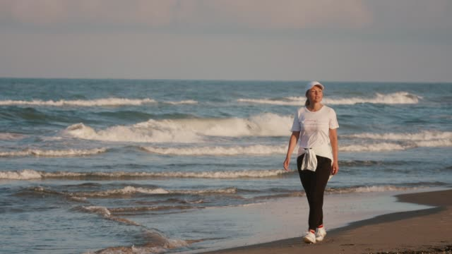 young woman in good mood walks along the ocean beach and enjoys morning sun and fresh air. happy calm harmony - active lifestyle stock videos & royalty-free footage