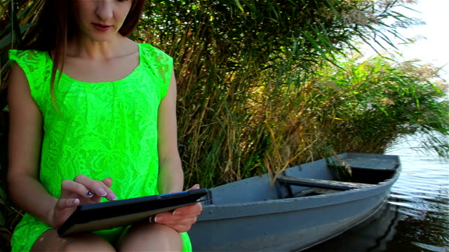 Young woman in green dress browsing photo on tablet