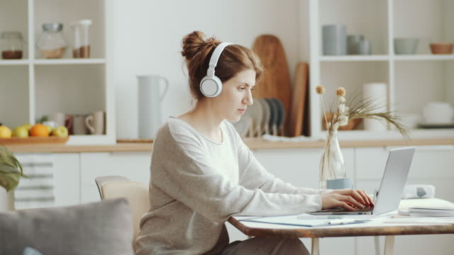 vídeos de stock e filmes b-roll de young woman in headphones messaging on laptop while working from home - remote work
