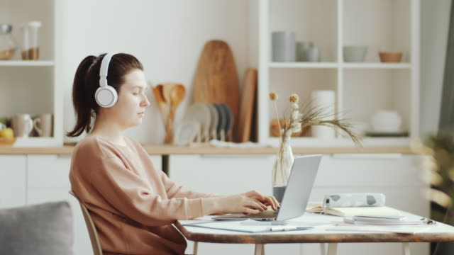 young woman in headphones working remotely on laptop from home - cuffie wireless video stock e b–roll